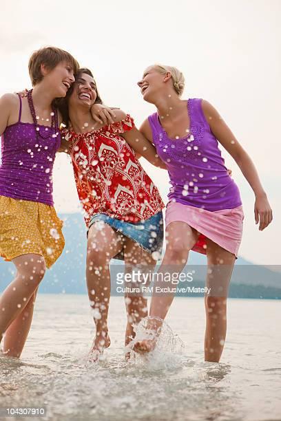 3 girls splashing feet in a lake