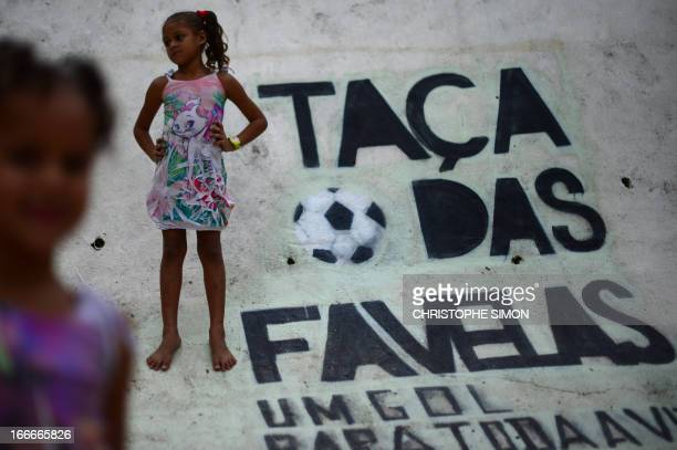 Girls stand next to a sign reading 'Shantytown's cup' on the wall of a football field in the Cidade de Deus shantytown Rio de Janeiro Brazil on April...