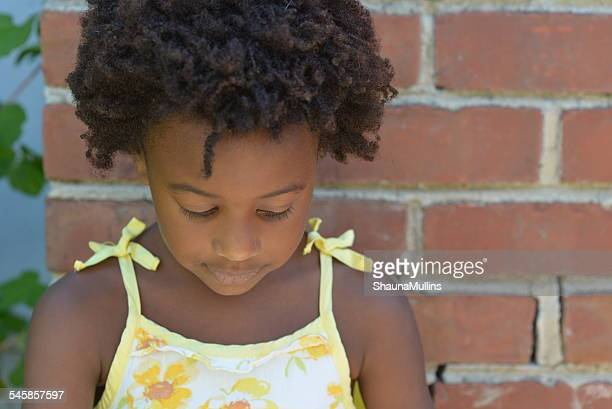 Girl (6-7) against brick wall