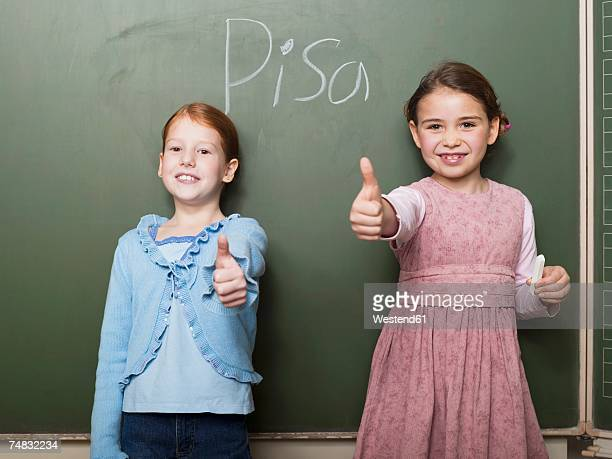 Girls (4-7) standing by blackboard, showing thumbs up sign