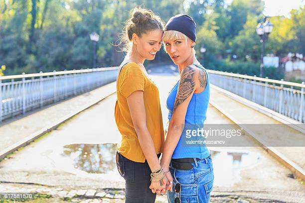 Girls standing face to face on bridge and holding hands
