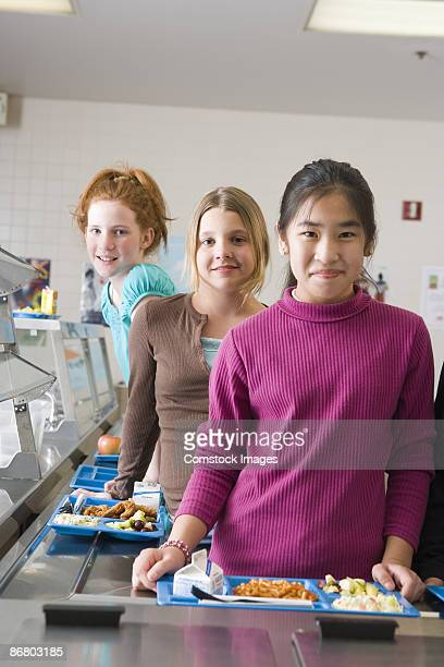 Girls standing in cafeteria with trays