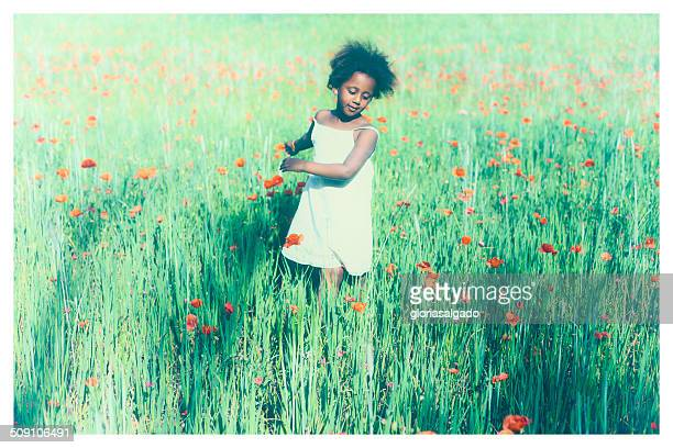 Girls standing in meadow with poppies