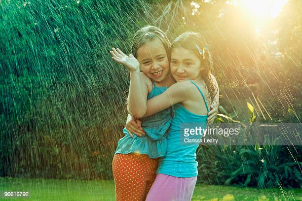 Girls standing in rain hugging
