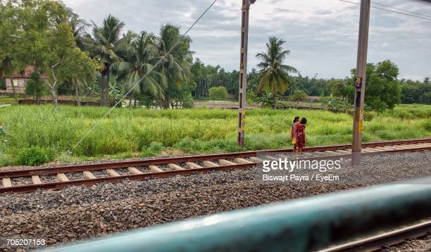 Girls Standing On Railroad Track By Grassy Field Against Sky