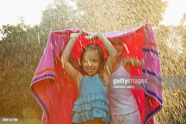 Girls standing under towel in rain