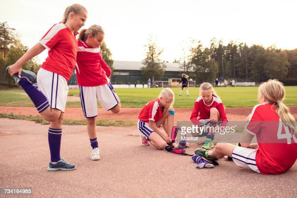 Girls stretching legs by friends wearing shin guards on field