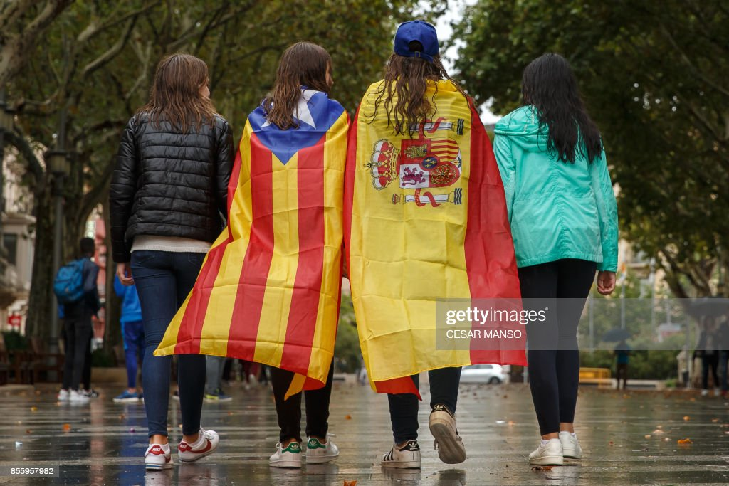 Girls stroll through the center of Figueras with the Spanish and a pro-independence 'Estelada' Catalan flag on September 30, 2017 in Figueras. Catalan separatists showed determination today to press ahead with an independence referendum banned by Madrid, occupying dozens of schools designated as polling stations to stop police from closing them down. /