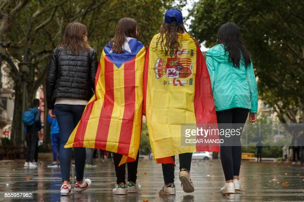 Girls stroll through the center of Figueras with the Spanish and a proindependence 'Estelada' Catalan flag on September 30 2017 in Figueras Catalan...
