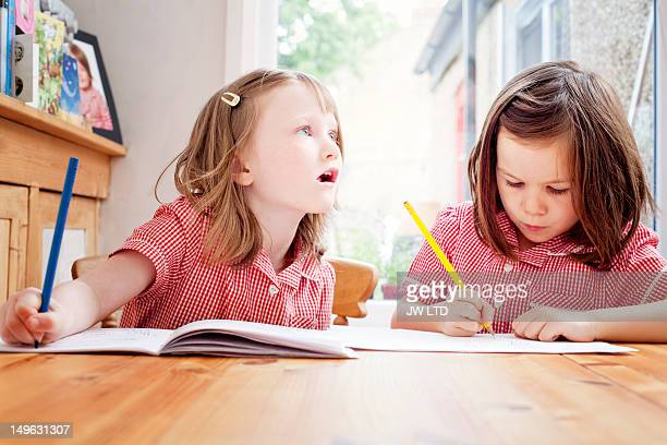 girls studying at kitchen table after school