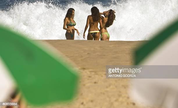 Girls sunbathe as a big wave brokes at Ipanema beach in Rio de Janeiro Brazil on April 24 2008 Due to the undertow the maritime passengers' traffic...