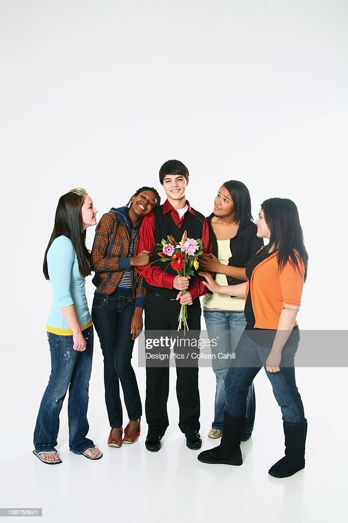 Girls Surrounding A Boy Who Is Holding Flowers