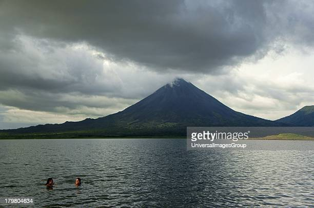 Girls swimming in Lake Arenal with Arenal Volcano in the background near La Fortuna Costa Rica