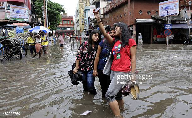 Girls take selfie as they wade through 2 feet deep water at Amherst Street on July 10 2015 in Kolkata India A heavy rainfall of 144 mm was recorded...
