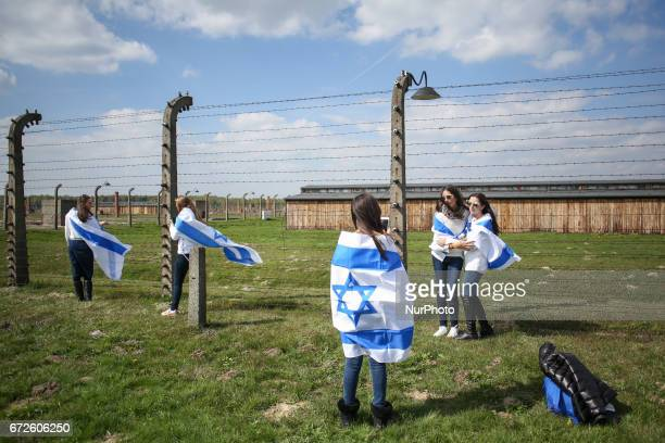 Girls taking photos by a barbed wire fence during the 'March of the Living' at the former NaziGerman Auschwitz Birkenau concentration and...