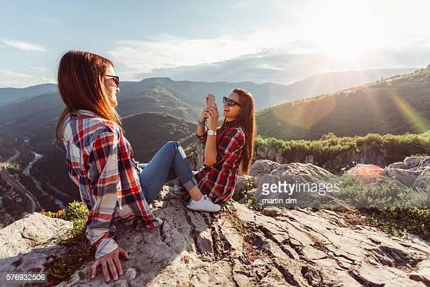 Girls taking photos on the mountain peak