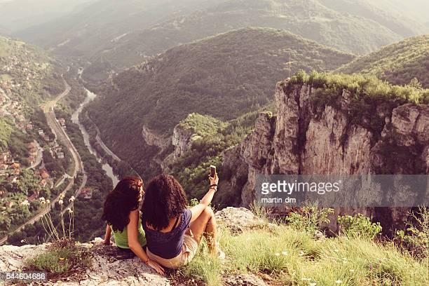 Filles prenant un selfie sur le sommet de la montagne