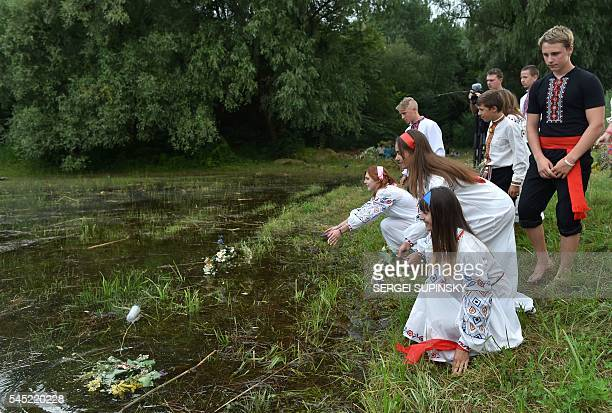 Girls throw flowers in a lake 'to find their grooms' during celebrations of the Ivana Kupala night an ancient heathen holiday in the Pyrogove village...