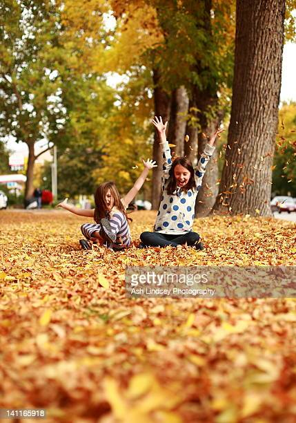 Girls throwing fallen leaves