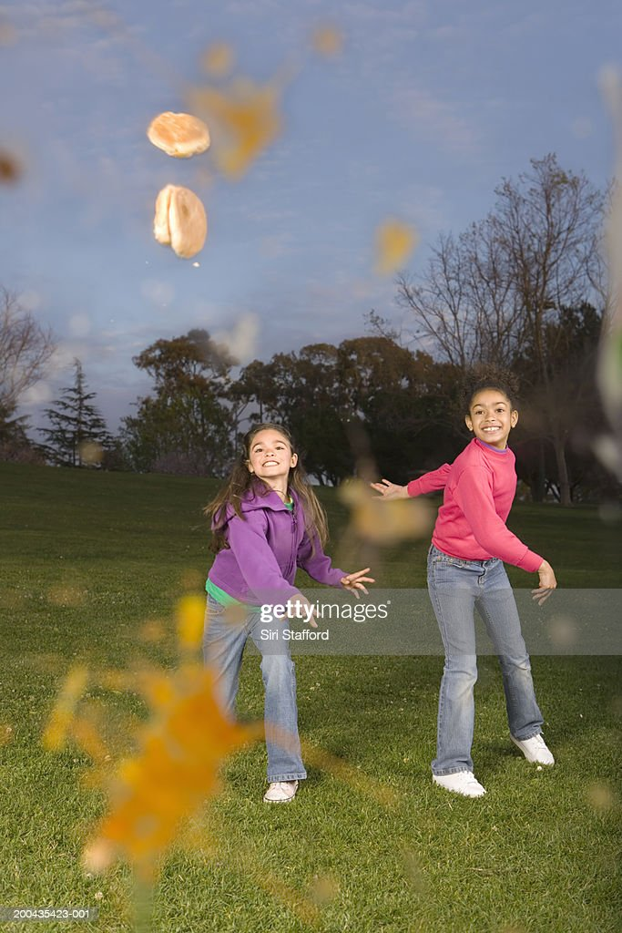 Girls (8-10) throwing food in park : Stock Photo