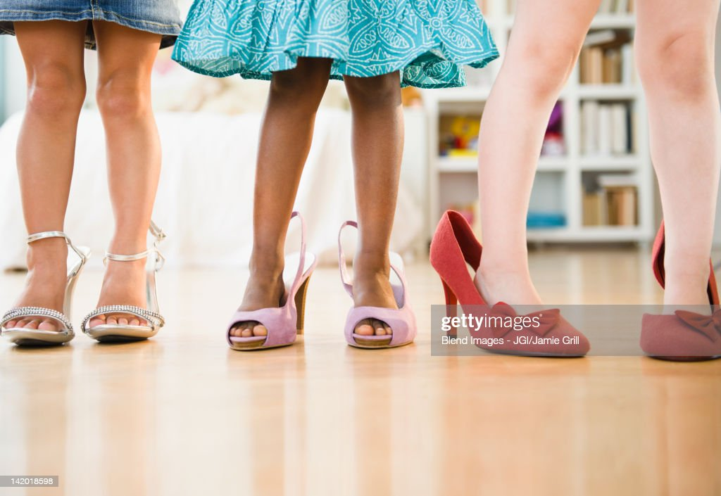 Girls trying on glamorous high-heeled shoes