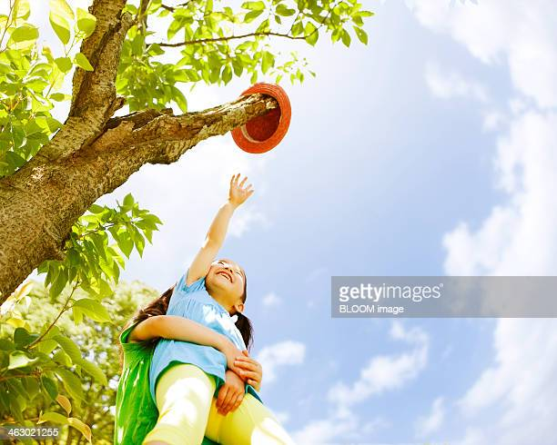 Girls Trying To Reach Hat On Tree