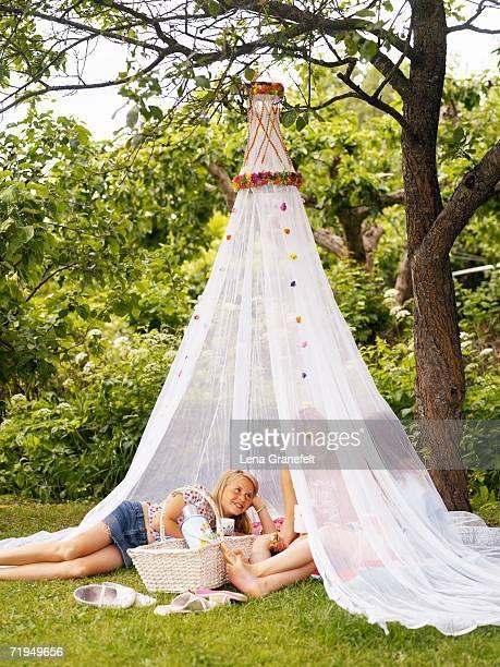 Girls under a mosquito net.