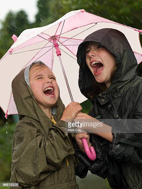 Girls under an umbrella singing