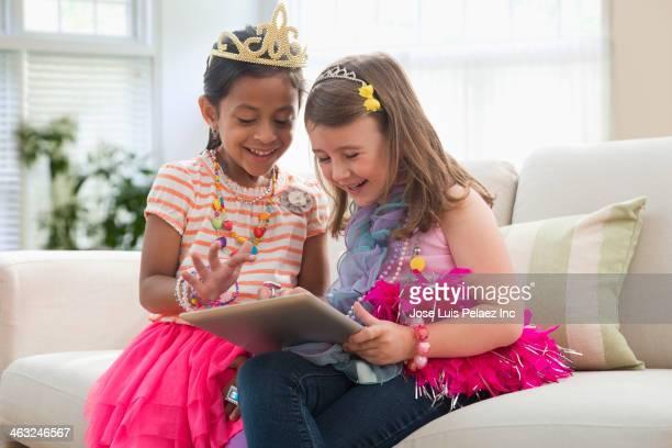 Girls using digital tablet on sofa