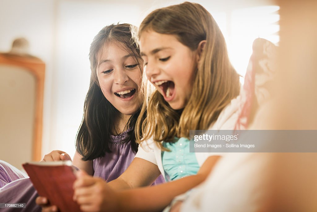 Girls using digital tablet together