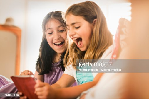 Girls using digital tablet together : Stock Photo