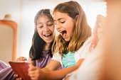 Girls using digital tablet together