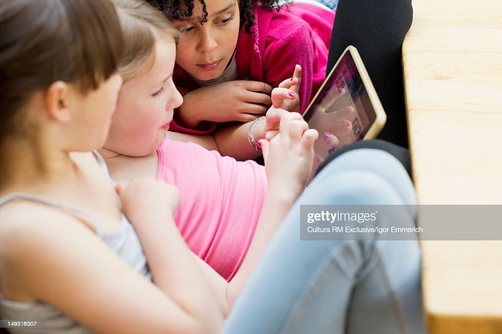 Girls using tablet computer together : Stock Photo