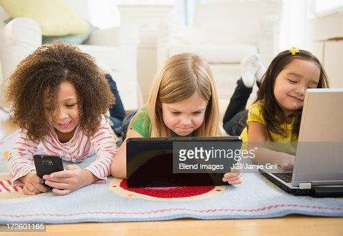 Girls using technology on carpet