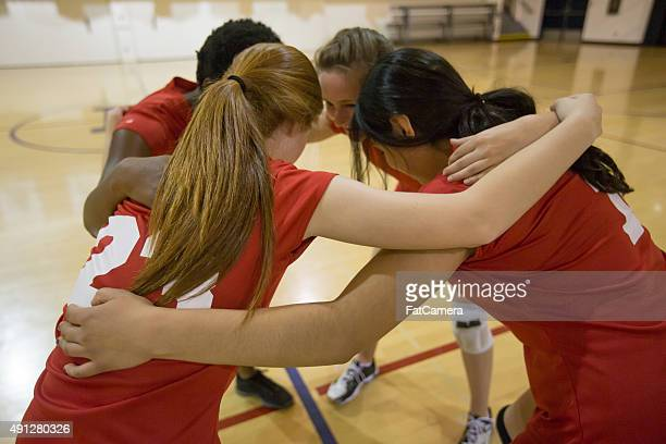 Girls volleyball players in team huddle