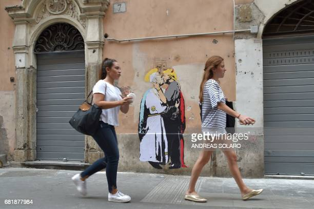 Girls walk past a collage showing Pope Francis kissing US President Donald Trump with a caption by artist TvBoy reading in English and Italian 'The...
