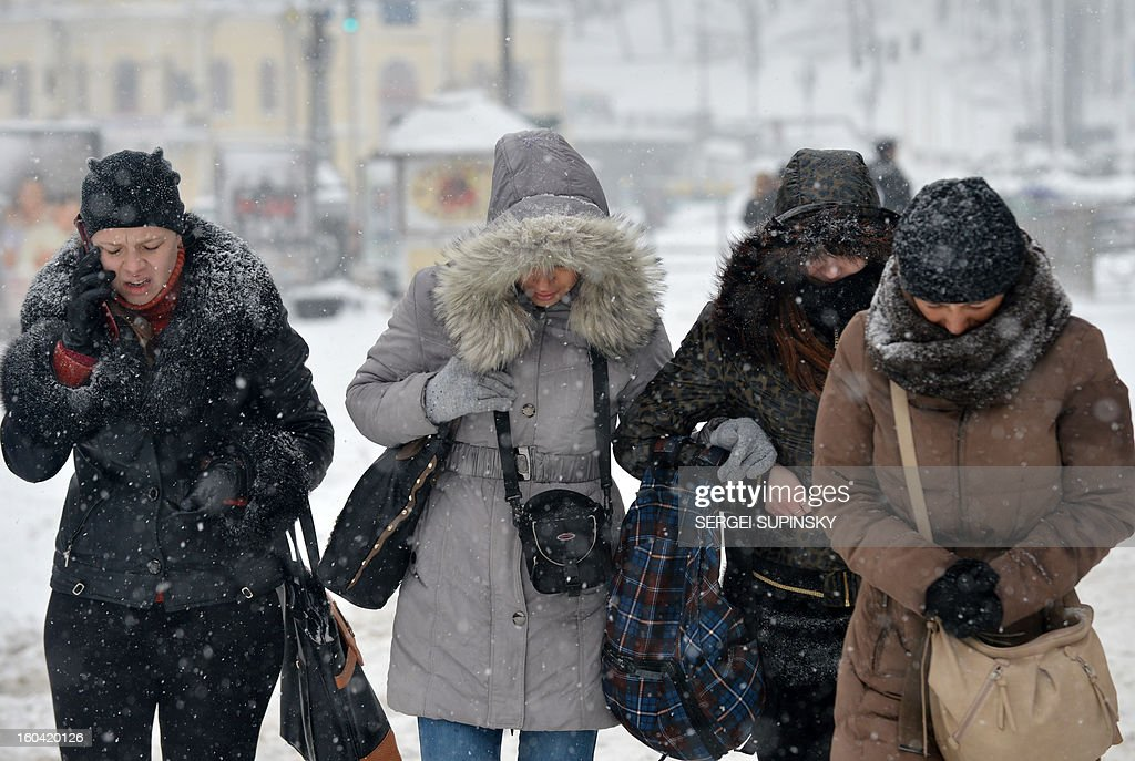 Girls walk under a heavy snow fall in Kiev on January 31, 2013. AFP PHOTO/SERGEI SUPINSKY