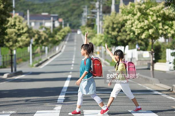 Girls walking across the road, raising hands, side view