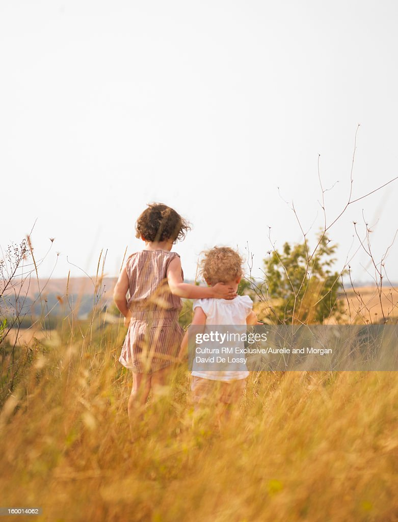 Girls walking together in grassy field : Stock Photo