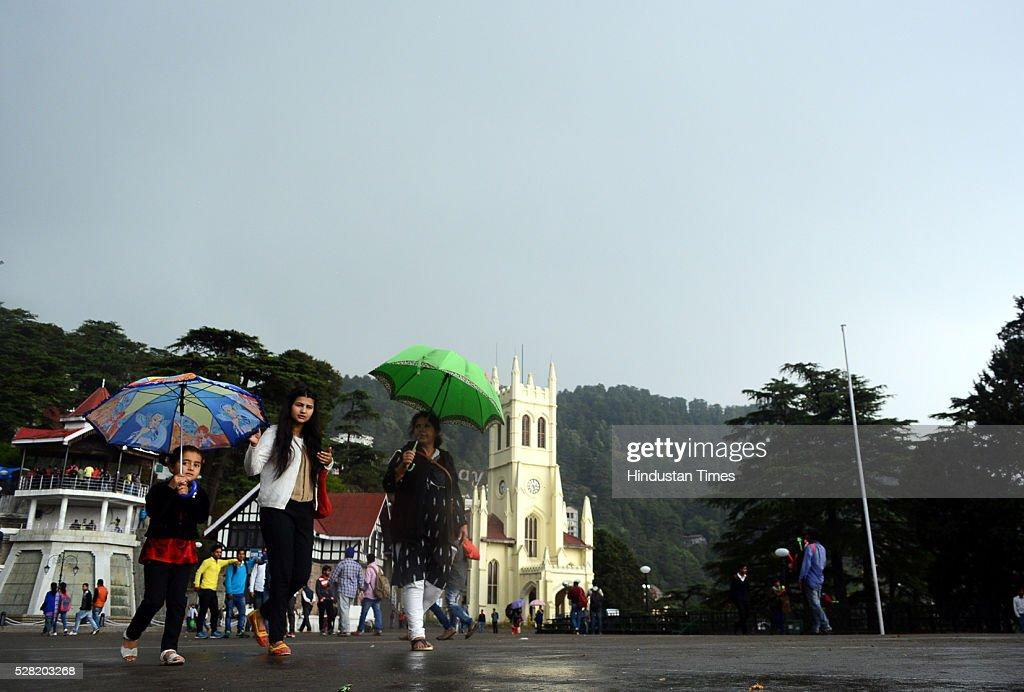 Girls walking with umbrella during rains at Ridge on May 4, 2016 in Shimla, India.