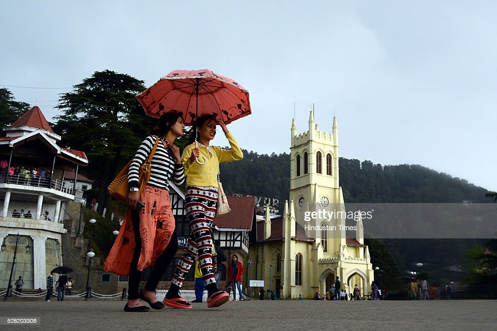 Girls walking with umbrella in rain at Ridge on May 4, 2016 in Shimla, India.