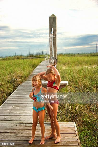 Girls washing at outdoor shower at beach