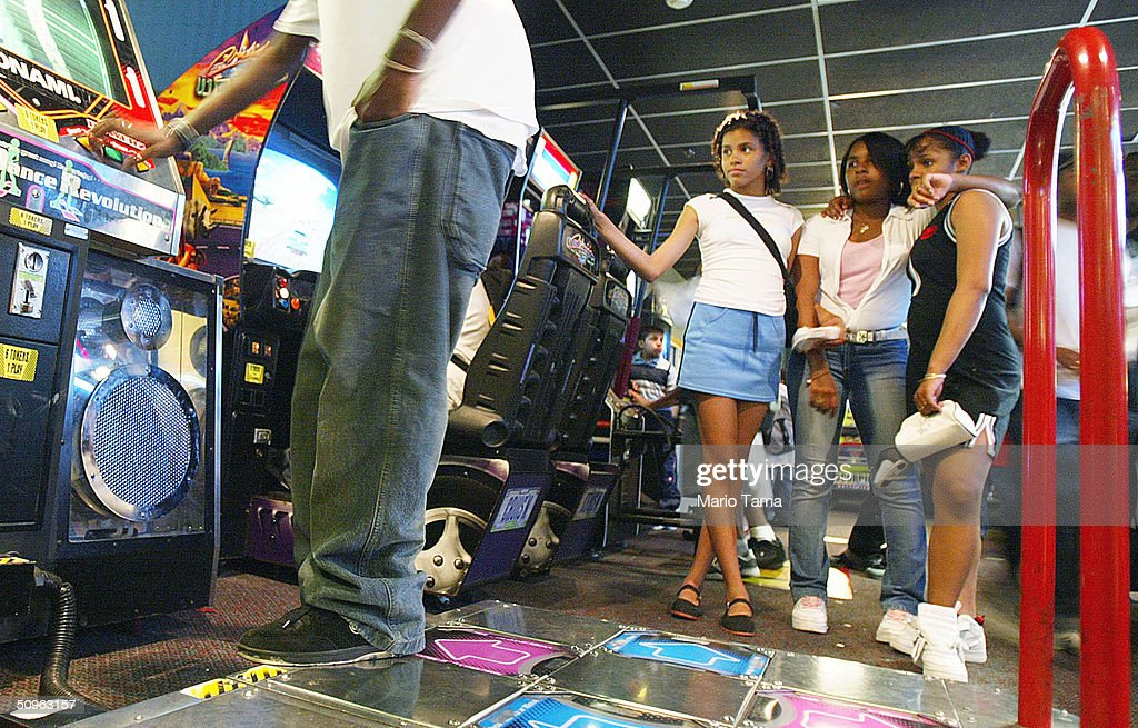 Girls watch as a player prepares to dance on the DDR or Dance Dance Revolution video game from Japan in a video game arcade June 15 2004 in New York...
