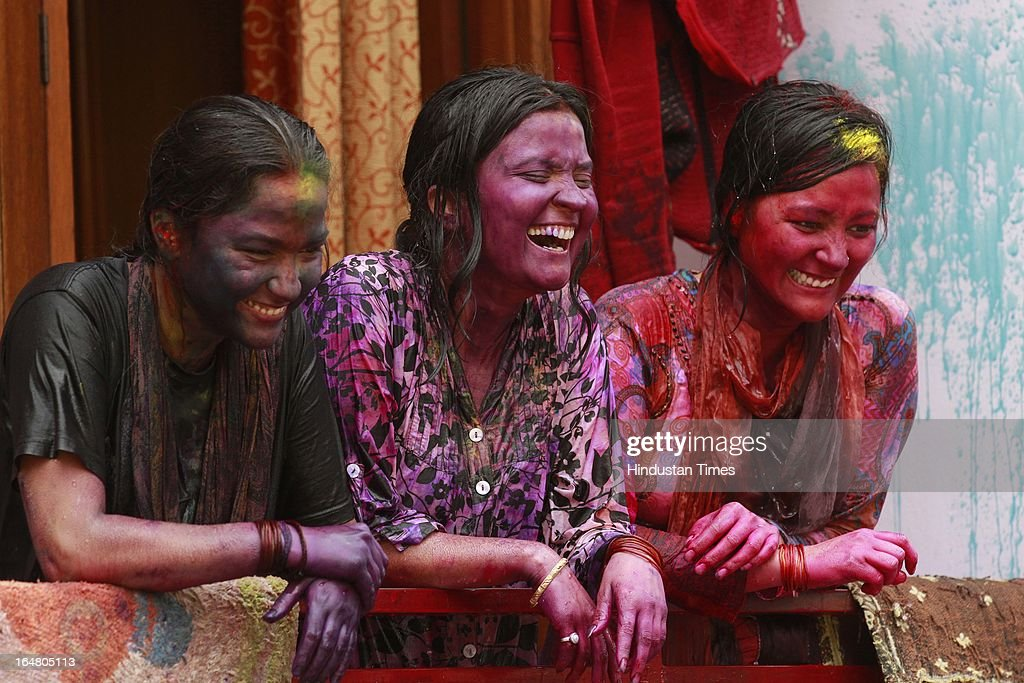 Girls watch from balcony after playing with colours during the Holi celebration on March 27, 2013 in New Delhi, India. Holi, festival of color is Hindu religious festival also called Basantotsav or spring festival as it mark the arrival of spring. People gather together to play colors, sing and dance to traditional tunes and eat sweets specially Gujiyas.