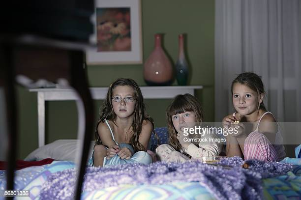 Girls watching television and eating popcorn
