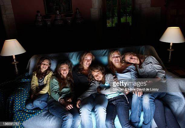 Girls watching television on sofa