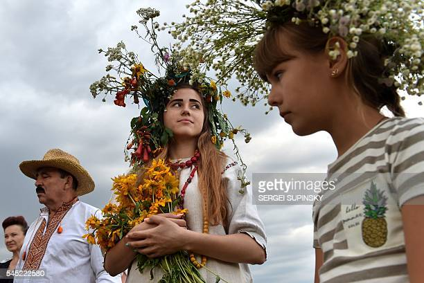 Girls wearing a wreath look at the bonfire during celebrations of the Ivana Kupala night an ancient heathen holiday in the Pyrogove village near Kiev...