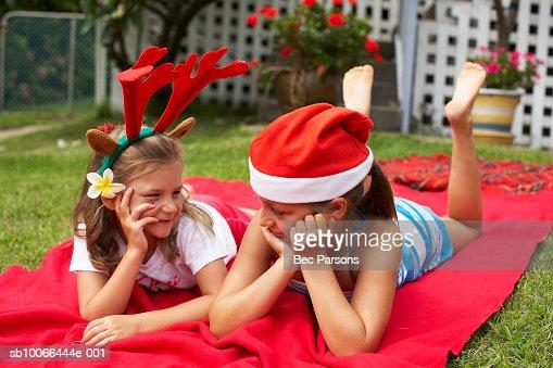 Niñas (7-9) usando sombrero de Navidad, caer en manta en prado : Foto de stock