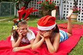 Niñas (7-9) usando sombrero de Navidad, caer en manta en prado