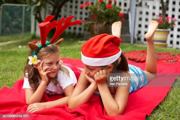 Filles (7 à 9) portant des chapeaux de Noël, allongé sur une couverture sur la pelouse